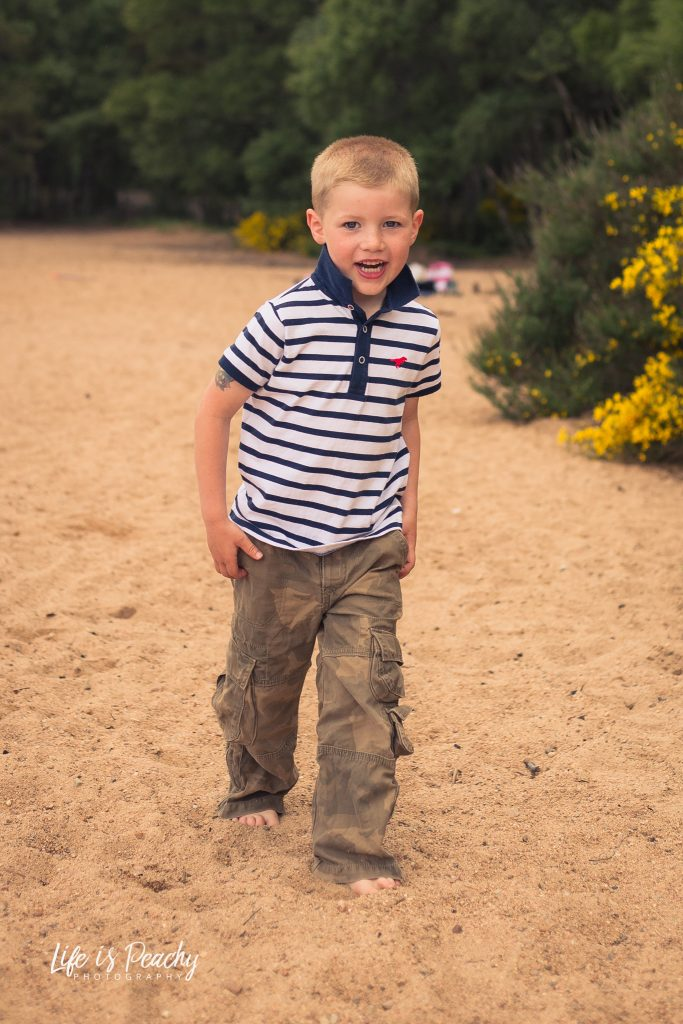 Boy walking on sand looking at camera. Loch Morlich, Highlands. Family photography, Aberdeenshire and Moray