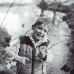 Boy smiling at camera holding stick - Leith Hall, Aberdeenshire