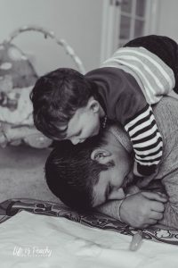 Boy hugging dad on floor Aberdeenshire Family Photographer