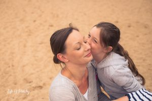 Girl cuddling mum on sand. Loch Morlich, Highlands. Family photographer Aberdeenshire and Moray