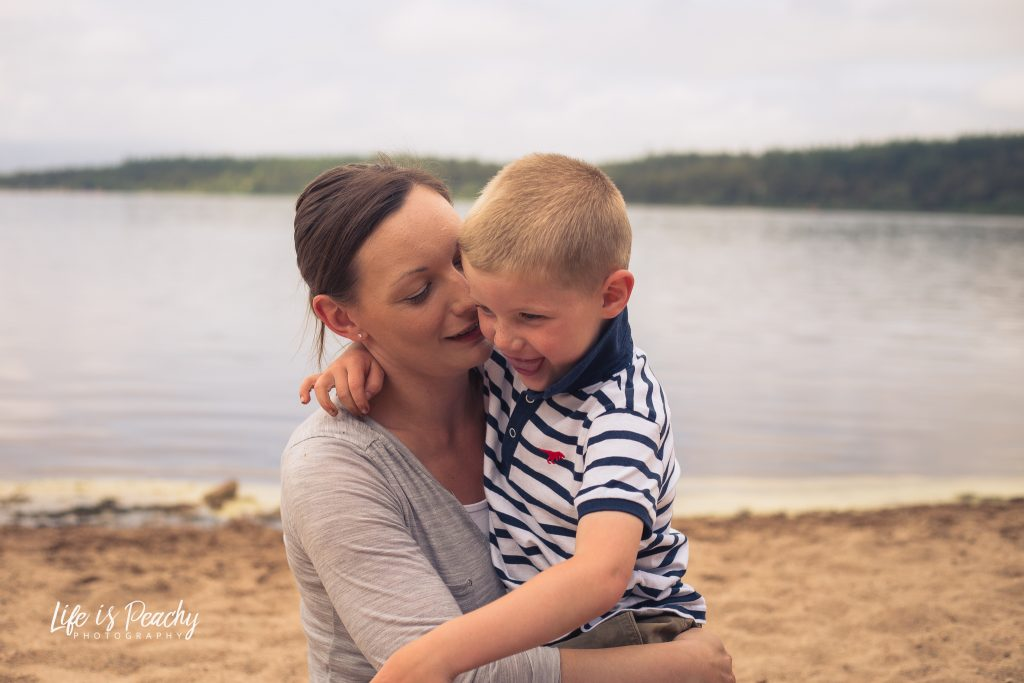 Mother cuddles son in front of water. Loch Morlich, Highlands. Family photography Aberdeenshire and Moray