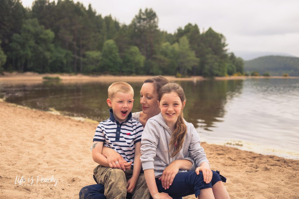 Family posing on beach. Loch Morlich, Highlands. Family photography, Aberdeenshire and Moray